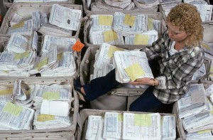 IRS Worker Amidst Baskets Full of Tax Forms