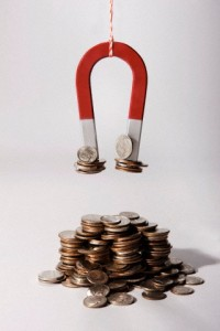 Magnet hanging on chain attracting coins