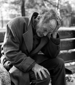 1960s 1970s destitute elderly man sitting on park bench with head in hands outdoor