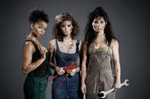 Three women in jumpsuits holding hand tools