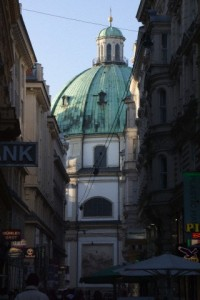 The dome of a old church at the end of a busy and narrow street.