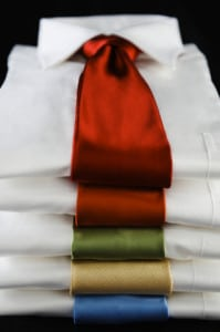 Stack of white button-down shirts and colorful neckties