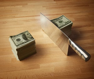 Meat Cleaver Cutting a Stack of Money in Half
