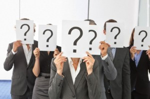 Businesspeople with question marks in front of their faces