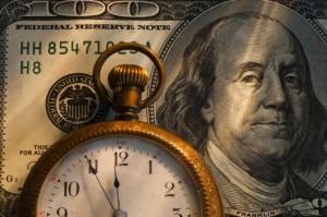 Pocket watch on one hundred dollar bill, studio shot