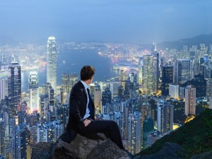 Businessman looking down on Victoria harbour, Hong Kong Island, Hong Kong, China